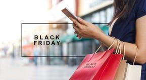 Black Friday, mulher que usa sacos de compras levando do smartphone imagens de stock
