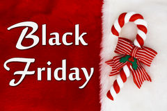 Black Friday. Red Plush background and a Candy Cane with text Stock Image