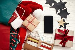 Black Friday sale. Christmas shopping and seasonal sale. Credi. T cards and money in wallet, phone with empty screen, paper bags with clothes, gift boxes on royalty free stock photography