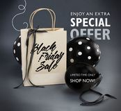 Black Friday sale banner containing recycled paper bag decorated with black satin ribbon, and black balloons. Grey background stock images