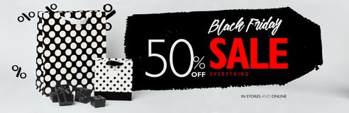 Black Friday sale banner, with small black gift-boxes, and black and white gift-bags with polka dots. Red and white letters stock photo