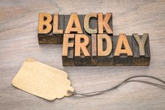 Black Friday sale banner in wood type. Black Friday concept  in vintage letterpress wood type blocks with a blank price tag against grained wood Stock Image