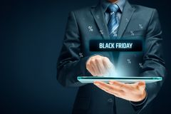 Black Friday sale. Concept. Businessman click on tablet on black Friday button, percentages on background Royalty Free Stock Photos