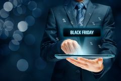 Black Friday sale. Concept. Businessman click on tablet on black Friday button, percentages on background royalty free stock image