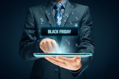 Black Friday sale. Concept. Businessman click on tablet on black Friday button, percentages on background royalty free stock photography