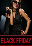 Black friday sale concept. Shopping woman holding bag on dark background in holiday stock images