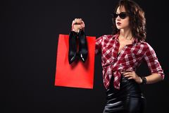 Black friday sale concept. Shopping woman holding bags isolated on dark background in holiday. stock images