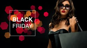 Black friday sale concept. Shopping woman holding grey bag isolated on dark background in holiday royalty free stock photos