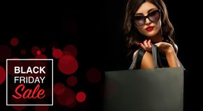 Black friday sale concept. Shopping woman holding grey bag isolated on dark background in holiday royalty free stock photo