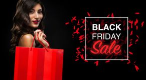 Black friday sale concept. Shopping woman holding red bag isolated on dark background in holiday stock image