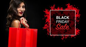 Black friday sale concept. Shopping woman holding red bag isolated on dark background in holiday royalty free stock photo