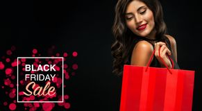 Black friday sale concept. Shopping woman holding red bag isolated on dark background in holiday stock images
