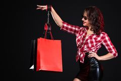 Black friday sale concept. Woman holding bags isolated on dark background. Handcuffed girl strapped to her bag. Hostage stock photos