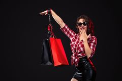 Black friday sale concept. Woman holding bags isolated on dark background. Handcuffed girl strapped to her bag. Hostage stock photography