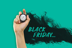 Black Friday sale - holiday shopping concept. The male hand holding a stopwatch against a yellow background. Black Friday sale - holiday shopping concept stock image