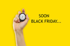 Black Friday sale - holiday shopping concept. The male hand holding a stopwatch against a yellow background. Black Friday sale - holiday shopping concept royalty free stock photography