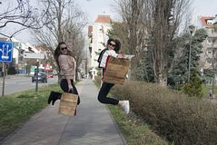 Black Friday 2019 sale - holiday shopping concept. Nice girls jump out of luck after shopping.With bags in your hands stock photos