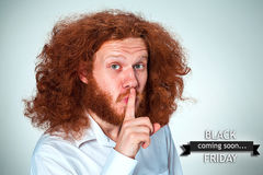 Black Friday sale - holiday shopping concept. The young man with long red hair looking at camera calling for silence. Black Friday sale - holiday shopping royalty free stock images