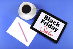 Black Friday Sale message on black computer tablet device. With cup of coffee on blue background Stock Photography