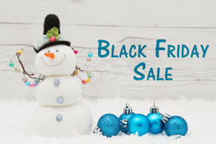 Black Friday sale message. Some snow, Christmas ornaments and a snowman on weathered wood with text Black Friday Sale Stock Image