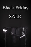 Black friday. Sale sign.  and white sneakers, cap  pant, jeans hanging on clothes rack   background. Royalty Free Stock Photo