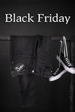 Black friday. Sale sign.  and white sneakers  pant, jeans hanging on clothes rack   background.  Close up. Royalty Free Stock Photo
