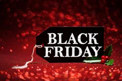 Black Friday sale tag. On red glitter background Stock Photo