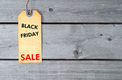 Black Friday sale tag. On brown vintage paper against wooden background Royalty Free Stock Image