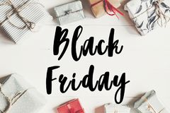 Black friday sale text. big sale offer discount sign on wrapped. Present boxes on white wooden background top view, space for text.  shopping concept Royalty Free Stock Image