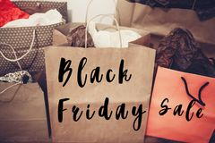 Black friday sale text. big sale offer discount sign on paper ba. G. many paper bags on background of white wall, christmas shopping, gifts and presents stock image