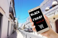 Black friday sale text on hand holding smart phone stock photo