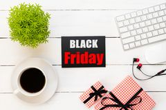 Black Friday Sale text on a red and black tag with coffee cup, plant table, gift box Earphone and mouse keyboard on white wooden royalty free stock photo