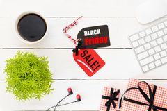 Black Friday Sale text on a red and black tag with coffee cup, plant table, gift box Earphone and mouse keyboard on white wooden stock photos