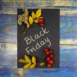 Black Friday Sale written on black card with leaves and wild rose fruits Stock Photography