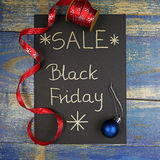 Black Friday Sale written on black card with red christmas ribbon Stock Photo