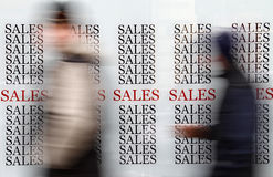 Black Friday sales. People passing by window shop with Black Friday sales signs Stock Image