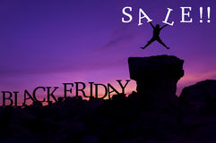 Black Friday sales concept. Silhouette man jumping on stone and holding word `Sale` - Black Friday sales concept Royalty Free Stock Images
