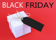 Black Friday Sales. A plain white box tied with a twine bow with a black tag on a red background. Black Friday sale message. Vertical image stock photo