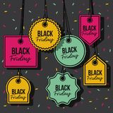 Black friday with set of discount offer tags in yellow magenta and green and pendant of threads in black background with. Confetti colorful vector illustration Stock Image
