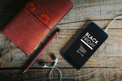 Black Friday shopping app in a mobile phone screen. Mobile phone on a wooden desk with Black Friday banner in the screen Royalty Free Stock Photos