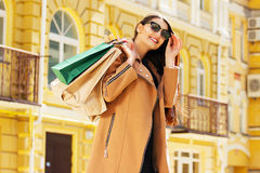 Black Friday shopping. Attractive and cheerful girl walking the city with shoppings. Shopping concept. Stock Images