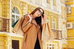Black Friday shopping. Attractive and cheerful girl walking the city with shoppings. Shopping concept. Royalty Free Stock Photography