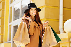 Black Friday shopping. Attractive and cheerful girl walking the city with shoppings. Shopping concept. Royalty Free Stock Photo