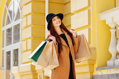 Black Friday shopping. Attractive and cheerful girl walking the city with shoppings. Shopping concept. Stock Image