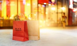 Black Friday shopping bags on floor in front of mall night. Black Friday shopping bags on floor front the mall store at night, business, retail, banner and sign Stock Photo