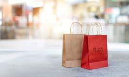 Black Friday shopping bags on floor outdoor. Black Friday shopping bags on the floor outdoors with the mall background stock photo