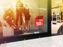 Black Friday shopping day sale. Window display with red sale board for Black Friday shopping. Blurred motion and vintage filter effect Stock Photo