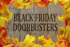 Black Friday Shopping Doorbusters. Autumn Leaves with grunge wood with text Black Friday Doorbusters Stock Image