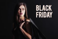 Black Friday Shopping. Elegant brunette woman wears black dress holding black shopping bags, black friday concept stock images