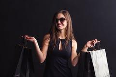 Black Friday Shopping. Elegant brunette woman wears sunglasses and black dress holding black shopping bags, black friday concept Stock Photography